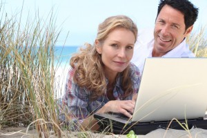 Couple with laptop on beach