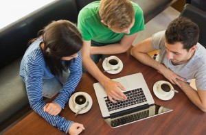 Overhead view of three students using laptop while having coffee at  the coffee shop